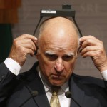 California Governor Jerry Brown adjusts his earpiece during a news conference at Memoria y Tolerancia museum in Mexico City